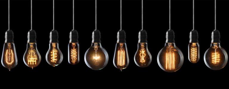 Verschieden geformte Leuchtmittel hängen nebeneinander aufgereiht von oben herab.