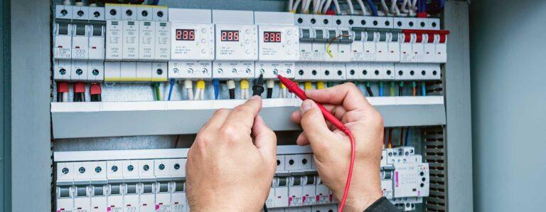 An einem Schaltschrank führt ein Fachmann die Prüfung nach DGUV V3 durch.