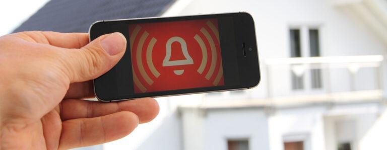 Ein Smartphone zeigt einen Einbruchalarm in einem dahinter stehenden Haus an.