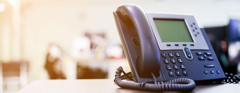 Schwarzes Telefon mit Schnur und großem Display zu einer Telefonanlage gehörend.